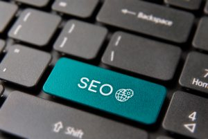 SEO business service keyboard button for online marketing concept. Search engine optimization icon key closeup in blue color.
